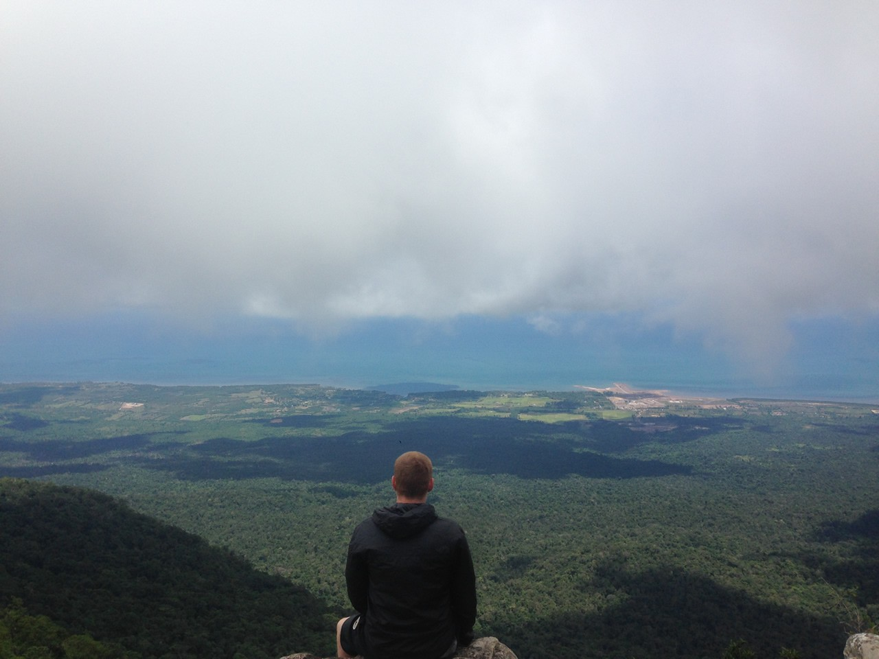 Picture of man sat on mountain looking at the sky